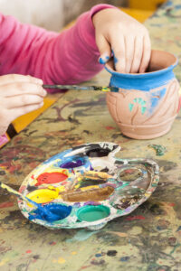 kid is colouring a vase made of pottery with watercolours from a watercolour palette